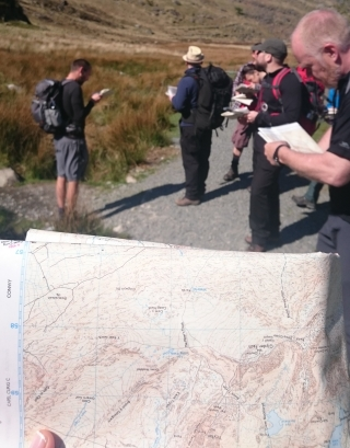 holding a map with a group of people outdoors